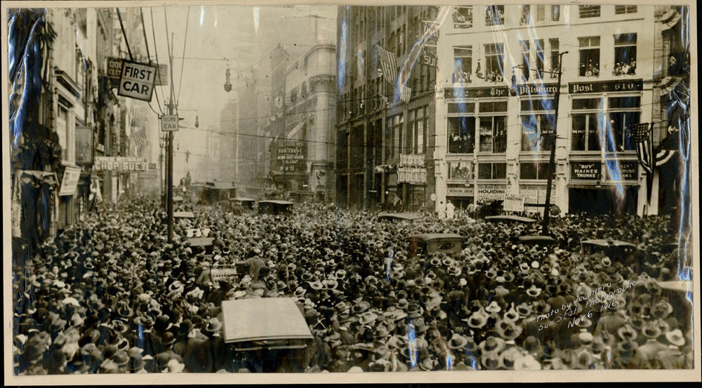 Photo of Houdini suspended above crowd in front of Pittsburgh Post building