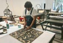 Member Alfonso Huerta carving his woodcut at the Flatbed Community Press