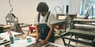 Member Alfonso Huerta carving his woodcut at the Flatbed Community Press