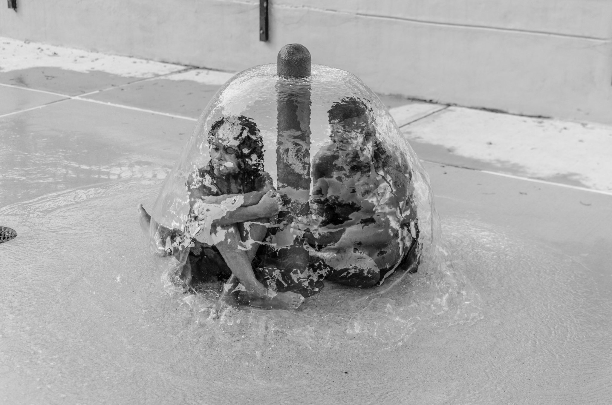 "Cindy Elizabeth, ""Kids huddle underneath a fountain at the Rosewood Park splashpad, Austin, Texas"" 2015. Digital photograph. @Cindy Elizabeth"
