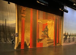 Vintage painted movie backdrops are exhibited on the Bass Concert Hall stage.